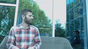 Dois homens comunicam-se em um café da rua em cadeiras de vime Dois amigos discutem memórias filme