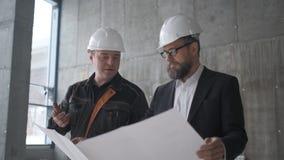 Dois homens consideráveis caucasianos nos capacetes que falam e que olham o papel grande com video estoque