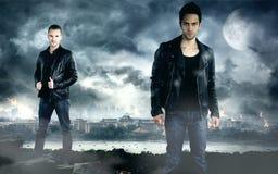 Dois homens consideráveis que levantam na frente da cidade escura fotografia de stock