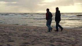Dois homens da Idade M?dia que andam junto na praia da areia no por do sol video estoque