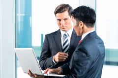 Dois homens de negócio com skyline do portátil e da cidade Imagens de Stock Royalty Free