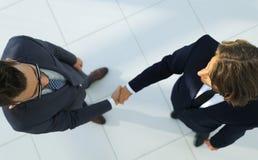 Dois homens de negócio que agitam as mãos no escritório Imagem de Stock