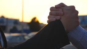 Dois homens de negócio que têm o aperto de mão amigável firme exterior com o alargamento do sol no fundo A agitação do homem arma video estoque