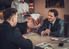 Dois homens de negócio seguros têm o almoço de negócio no restaurante Imagens de Stock