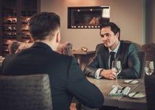 Dois homens de negócio seguros têm o almoço de negócio no restaurante Fotos de Stock Royalty Free