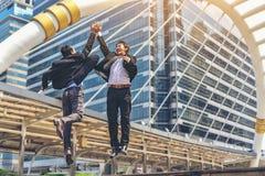 Dois homens de negócios asiáticos são deleitados e saltar, tocando em cada o imagem de stock royalty free