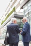 Dois homens de negócios de cabelo cinzentos superiores que andam abaixo da rua e que falam, vista traseira foto de stock