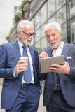 Dois homens de negócios de cabelo cinzentos superiores que falam na frente de um prédio de escritórios fotografia de stock