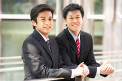 Dois homens de negócios chineses fora do escritório moderno Fotografia de Stock Royalty Free