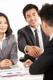 Dois homens de negócios chineses que agitam as mãos durante a reunião Imagem de Stock Royalty Free