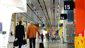 Dois homens de negócios com bagagem de mão seguem o terminal de aeroporto vídeos de arquivo