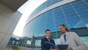 Dois homens de negócios comparam os originais do projeto com o resultado final video estoque