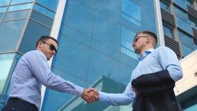 Dois homens de negócios consideráveis bem sucedidos que encontram e que agitam as mãos perto do prédio de escritórios Gerentes no filme