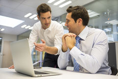 Dois homens de negócios consideráveis que trabalham junto em um projeto no de Imagens de Stock Royalty Free