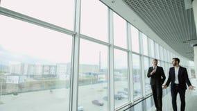 Dois homens de negócios conversam junto enquanto andam avante através de um prédio de escritórios moderno ocupado