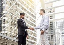 Dois homens de negócios de sorriso que agitam as mãos junto Fotos de Stock