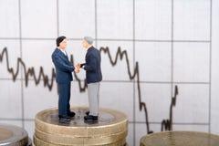 Dois homens de negócios em moedas Fotografia de Stock Royalty Free