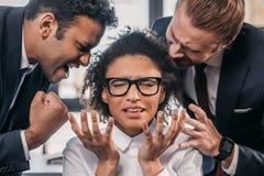 Dois homens de negócios emocionais no formalwear que gritam na mulher de negócios no escritório Imagens de Stock