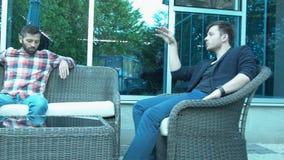 Dois homens de negócios estão discutindo um projeto comum em uma atmosfera relaxado Os dois homens estão falando seriamente na ru filme