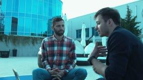 Dois homens de negócios estão olhando a tabuleta que discutem o projeto fora do hotel O patrocinador e o protegido comunicam-se vídeos de arquivo
