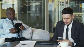 Dois homens de negócios multi-étnicos na roupa formal que senta e que usa seus smartphone e tabuleta no café vítreo durante o alm video estoque