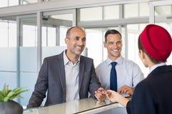 Dois homens de negócios no aeroporto verificam dentro foto de stock
