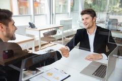 Dois homens de negócios novos bem sucedidos alegres que agitam as mãos na reunião de negócios Imagens de Stock Royalty Free