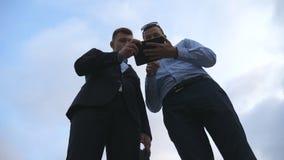 Dois homens de negócios novos que falam e que usam o PC da tabuleta exterior Homens de negócio que trabalham na tabuleta digital  Imagens de Stock