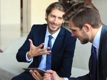 Dois homens de negócios novos que usam o touchpad na reunião foto de stock