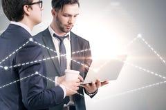 Dois homens de negócios novos sobre o cinza, primeiro plano do gráfico foto de stock