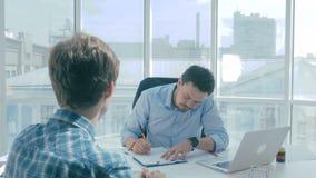 Dois homens de negócios que assinam o contrato no escritório moderno video estoque