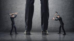 Dois homens de negócios que batem os pés gigantes de outros com martelos em um fundo concreto Fotos de Stock