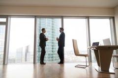Dois homens de negócios que estão na janela completo no escritório, café foto de stock