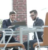 Dois homens de negócios que trabalham junto usando o portátil na reunião de negócios no escritório Fotografia de Stock Royalty Free