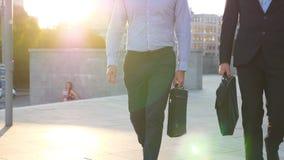 Dois homens de neg?cios com pastas que andam na rua da cidade com o alargamento do sol no fundo Os s?cios comutam para trabalhar  filme