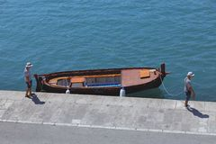 Dois homens dos marinheiros e o barco no cais escuro-azul na separação fotos de stock royalty free