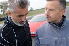Dois homens e carro rápido fotos de stock royalty free