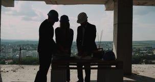 Dois homens e a mulher no canteiro de obras que olha através do original e analisam o projeto 4K filme