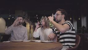 Dois homens e tinidos da mulher seus glases com o vinho tinto que senta-se na tabela no restaurante turco moderno Os amigos têm filme