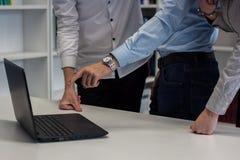 Dois homens e uma mulher que trabalha em um projeto incorporado Homem no b Imagens de Stock Royalty Free
