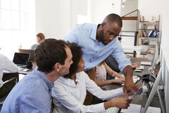 Dois homens e uma mulher que trabalha junto no escritório de plano aberto Foto de Stock Royalty Free