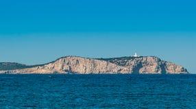 Dois homens em um barco dirigem ao farol em Ibiza ilhas ensolaradas de Conejera, St Antoni de Portmany Balearic Islands, Espanha Imagens de Stock Royalty Free