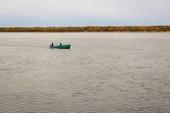Dois homens em um flutuador do barco de enfileiramento ao longo do rio imagem de stock