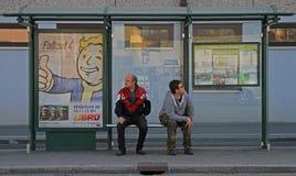 Dois homens estão esperando o transporte na parada do ônibus Foto de Stock Royalty Free