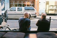 Dois homens estão sentando-se fora da cafetaria, Dublin, Irlanda 2015 09 30 Foto de Stock Royalty Free