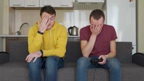 Dois homens est?o jogando jogos de v?deo e perdem-nos video estoque