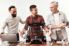 Dois homens estabelecem uma impressora 3d, umas posses idosas de um homem um portátil em suas mãos e uns relógios o processo Imagem de Stock Royalty Free