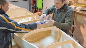 Dois homens fazem independentemente um barco da madeira Eles mesmos inventaram o projeto da embarcação para seus cursos vídeos de arquivo