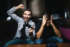 Dois homens felizes novos que jogam jogos de vídeo ao sentar-se no sofá fotografia de stock royalty free