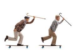 Dois homens idosos com os bastões que montam longboards fotografia de stock royalty free